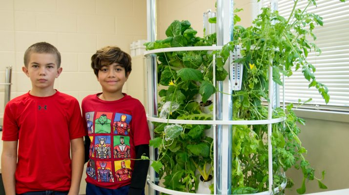 Two Students Standing in Front of Tower Garden