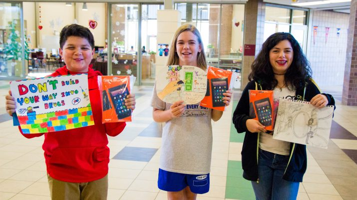 Three Students Standing with Kindle Fires in Hand